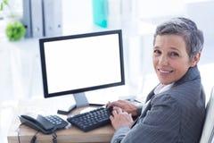 Femme d'affaires de sourire à l'aide de l'ordinateur Photographie stock libre de droits