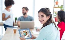 Femme d'affaires de sourire à l'aide de la tablette Images stock