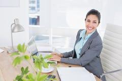 Femme d'affaires de sourire à l'aide de son ordinateur Photos libres de droits