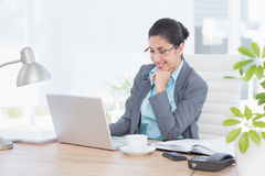 Femme d'affaires de sourire à l'aide de son ordinateur Images stock