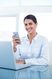 Femme d'affaires de sourire à l'aide de son smartphone Images stock