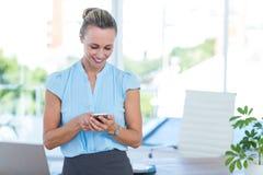 Femme d'affaires de sourire à l'aide de son smartphone Photos stock