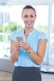 Femme d'affaires de sourire à l'aide de son smartphone Image libre de droits
