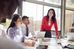 Femme d'affaires de sourire écoutant des collègues lors d'une réunion photos libres de droits
