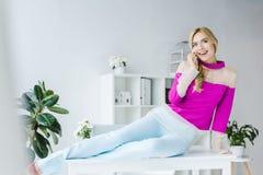 femme d'affaires de sourire élégante s'asseyant sur la table et parlant sur le smartphone Photo stock