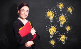 Femme d'affaires de sourire attirante devant un tableau noir avec beaucoup d'ampoules image libre de droits