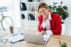 femme d'affaires de sourire attirante s'asseyant à la table avec l'ordinateur portable dans le bureau et le regard images stock