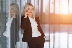 Femme d'affaires de sourire au téléphone regardant l'appareil-photo dans un bureau Photographie stock