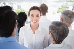 Femme d'affaires de sourire avec des collègues de nouveau à l'appareil-photo Photo libre de droits