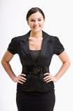 Femme d'affaires de sourire avec des mains sur des gratte-culs photographie stock libre de droits
