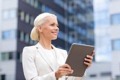 Femme d'affaires de sourire avec le PC de comprimé dehors Images stock