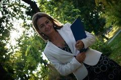 Femme d'affaires de sourire avec le presse-papiers en parc images stock