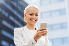 Femme d'affaires de sourire avec le smartphone dehors Images libres de droits