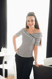 Femme d'affaires de sourire avec un sourire parfait se penchant contre une chaise et regarder l'appareil-photo Photographie stock libre de droits