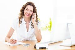 Femme d'affaires de sourire ayant l'appel téléphonique Image stock