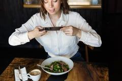 Femme d'affaires de sourire ayant le lucnch au café à l'intérieur photo stock
