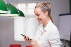 Femme d'affaires de sourire blonde à l'aide du smartphone Image libre de droits