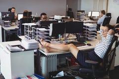 Femme d'affaires de sourire détendant tandis que collègues travaillant dans le bureau image libre de droits