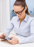 Femme d'affaires de sourire dans des lunettes avec le PC de comprimé Image stock