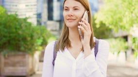 Femme d'affaires de sourire dans la chemise blanche se tenant au district des affaires du centre parlant sur le smartphone clips vidéos