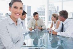 Femme d'affaires de sourire de brune lors d'une réunion image libre de droits
