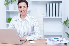 Femme d'affaires de sourire de jolie brune à l'aide de l'ordinateur portable Image libre de droits