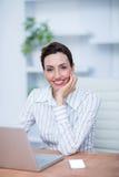 Femme d'affaires de sourire de jolie brune à l'aide de l'ordinateur portable Photographie stock