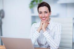 Femme d'affaires de sourire de jolie brune à l'aide de l'ordinateur portable Photos stock