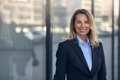 Femme d'affaires de sourire devant un vitrail Photographie stock libre de droits