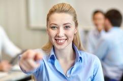 Femme d'affaires de sourire dirigeant le doigt sur vous Photographie stock libre de droits