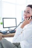 Femme d'affaires de sourire employant l'ordinateur et téléphoner Image libre de droits