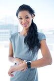 Femme d'affaires de sourire employant son smartwatch Image libre de droits