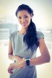 Femme d'affaires de sourire employant son smartwatch Photographie stock libre de droits
