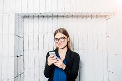 Femme d'affaires de sourire en verres ayant l'appel visuel par l'intermédiaire du téléphone portable, se tenant contre le mur de  photographie stock