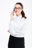 Femme d'affaires de sourire en verres se tenant et parlant au téléphone portable Image stock