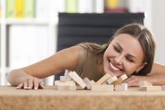 Femme d'affaires de sourire et une tour en bois tombée Image stock