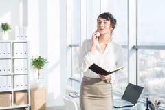 Femme d'affaires de sourire heureuse ayant un appel d'affaires, discutant des réunions, prévoyant son jour de travail, utilisant  Images libres de droits