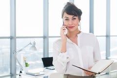 Femme d'affaires de sourire heureuse ayant un appel d'affaires, discutant des réunions, prévoyant son jour de travail, utilisant  Photographie stock libre de droits