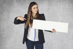 Femme d'affaires de sourire indiquant l'endroit sur votre publicité Photos stock