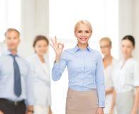 Femme d'affaires de sourire montrant le correct-signe avec la main Image stock