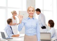 Femme d'affaires de sourire montrant le correct-signe avec la main Photo stock