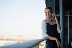 Femme d'affaires de sourire parlant au téléphone dans le balcon Image stock
