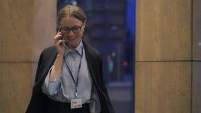 Femme d'affaires de sourire parlant au téléphone marchant dans la rue de soirée clips vidéos