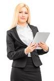 Femme d'affaires de sourire portant le costume noir, tenant un comprimé Photographie stock libre de droits