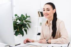 femme d'affaires de sourire regardant l'écran d'ordinateur sur le lieu de travail image libre de droits