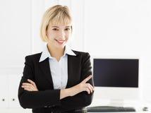 Femme d'affaires de sourire restant dans le bureau Photographie stock