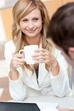 Femme d'affaires de sourire retenant une cuvette de café Photographie stock