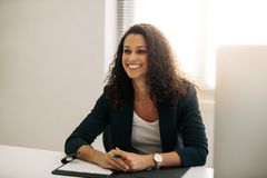 Femme d'affaires de sourire s'asseyant à son bureau dans le bureau photos stock