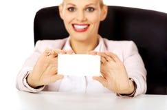 Femme d'affaires de sourire s'asseyant derrière le bureau et tenant la carte de visite professionnelle de visite vide Photographie stock