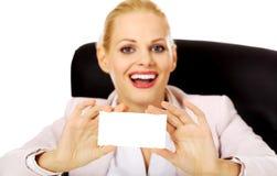 Femme d'affaires de sourire s'asseyant derrière le bureau et tenant la carte de visite professionnelle de visite vide Photos stock